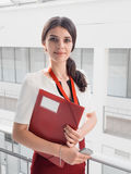 Beautiful Smiling Businesswoman Standing Against White Offices Background. Portrait of Business Woman With a Folder in Her Hands Stock Image