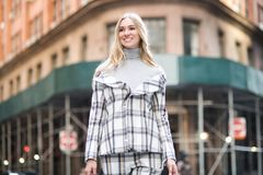 Beautiful smiling businesswoman walking on city street wearing stylish outfit suit. stock images