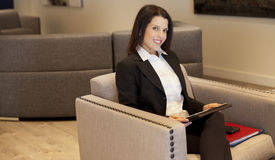 Beautiful Smiling Businesswoman working on tablet at the hotel Royalty Free Stock Photography
