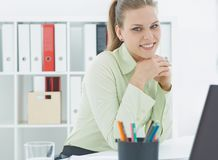 Young beautiful smiling businesswomansitting at her workplace at office. Business, exchange market, job offer, analytics. Beautiful smiling businesswomansitting Stock Images