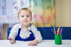 Beautiful smiling caucasian boy 3 years old drawing with colored pencil in a notebook sitting at a desk in a classroom in a kinder royalty free stock photography