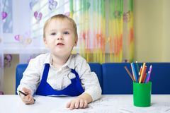 Beautiful smiling caucasian boy 3 years old drawing with colored pencil in a notebook sitting at a desk in a classroom in a kinder stock photography