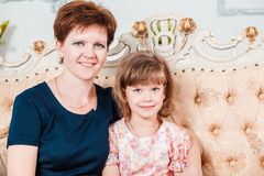 Beautiful smiling Caucasian mother and daughter looking at camera royalty free stock images