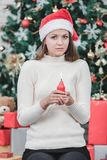 Beautiful smiling Caucasian woman wears red santacros hat and white top holding a lighten candle. stock photos