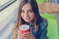 Beautiful smiling cheerful excited happy nice glad cute lovely woman with big eyes and charming smile holding a cup of delicious c. Offee with foam. She is royalty free stock photo