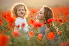 Beautiful smiling child girl with mother are having fun in field of red poppy flowers over sunset lights. Beautiful happy couple mother and cute daughter are royalty free stock photography