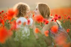 Beautiful smiling child girl with mother are having fun in field of red poppy flowers over sunset lights. Beautiful happy couple mother and cute daughter are royalty free stock photo