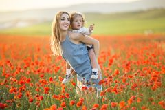 Beautiful smiling child girl with mother are having fun in field of red poppy flowers over sunset lights, spring time. Beautiful happy couple mother and cute stock image
