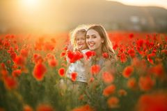 Beautiful smiling child girl with young mother are having fun in field of poppy flowers over sunset lights. Beautiful couple mother and cute daughter are walking stock photo