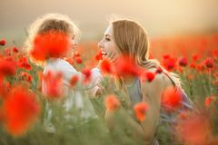 Beautiful smiling child girl with young mother are having fun in field of poppy flowers over sunset lights. Beautiful couple mother and cute daughter are walking royalty free stock image