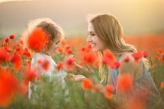 Beautiful smiling child girl with young mother are having fun in field of poppy flowers over sunset lights. Beautiful couple mother and cute daughter are walking stock image