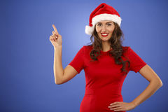 Beautiful smiling christmas santa woman pointing up showing copy Stock Photos