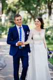 Beautiful smiling couple go holding hands in the park Stock Photo