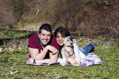 Beautiful smiling couple having fun with  their white dog outdoor Royalty Free Stock Photos