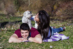 Beautiful smiling couple having fun with  their white dog outdoor Royalty Free Stock Images