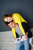 Beautiful smiling couple holding word LOVE , sitting together on gray background Royalty Free Stock Photo