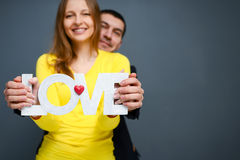 Beautiful smiling couple holding word LOVE , standing together on gray background Royalty Free Stock Photos