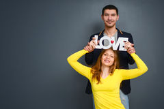Beautiful smiling couple holding word LOVE , standing together on gray background Royalty Free Stock Images
