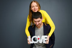 Beautiful smiling couple holding word LOVE , standing together on gray background Stock Photo