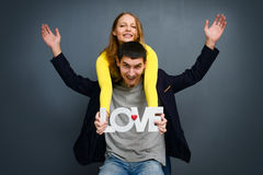 Beautiful smiling couple holding word LOVE , standing together on gray background Royalty Free Stock Image