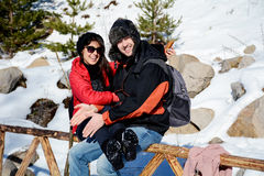 Beautiful smiling couple hugging and smiling in the winter mountain Stock Images