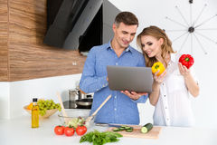 Beautiful smiling couple using laptop and making salad Royalty Free Stock Images