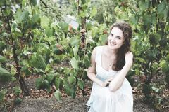 Beautiful curly hair girl in a light blue simple dress in a vineyard. Beautiful smiling curly hair brunette in a light blue simple dress having a break in a royalty free stock photos