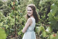 Beautiful curly hair girl in a light blue simple dress in a vineyard. Beautiful smiling curly hair brunette in a light blue simple dress in a vineyard stock images