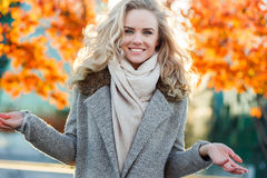 Beautiful smiling cute blonde girl on background of autumn tree Royalty Free Stock Photography