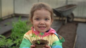 Beautiful smiling cute preschool girl in greenhouse. Beautiful adorable cute laughing smiling girl in secret garden.