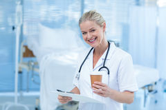 Beautiful smiling doctor holding clipboard and goblet Royalty Free Stock Photography