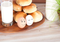 Beautiful smiling eggs with milk, bun and easter basket of grass Royalty Free Stock Images