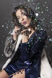 Beautiful, smiling, elegant brunette woman, dressed in a brilliant blue dress and fur coat, sits on a chair and throws festive royalty free stock image