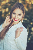 Beautiful smiling elegant woman in white shirt with pearl earrings. And long hair in the park at sunny day Stock Images