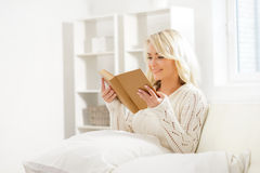 Beautiful smiling excited woman reading a book in the morning Royalty Free Stock Images