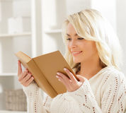 Beautiful smiling excited woman reading a book in the morning Stock Image