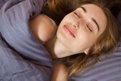 Beautiful smiling face of a young woman sleeping in bed close up royalty free stock image