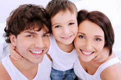 Beautiful smiling faces of people. Beautiful smiling faces of  people. A happy young family from three persons Royalty Free Stock Image