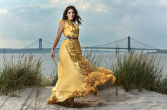 Beautiful smiling fashion model in elegant designers dress posing on the beach Royalty Free Stock Image