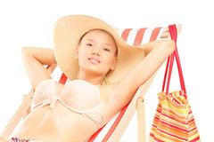 Beautiful smiling female in bikini enjoying on a beach chair Stock Images