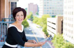Beautiful smiling female, businesswoman, relaxing on a balcony on a sunny summer day, reading a newspaper Royalty Free Stock Photography