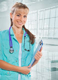 Beautiful smiling female doctor holding clipboard and looking at Stock Photos