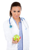 Beautiful smiling female doctor or nurse with stethoscope offering you a green apple Stock Images