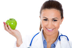 Beautiful smiling female doctor or nurse with stethoscope offering you a green apple Royalty Free Stock Photos