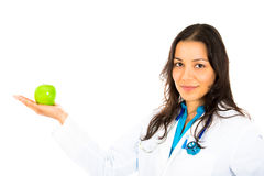Beautiful smiling female doctor or nurse with stethoscope offering you a green apple Royalty Free Stock Photography