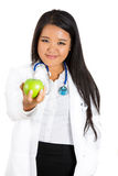 beautiful smiling female doctor or nurse with stethoscope offering you a green apple Stock Image