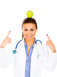 Beautiful smiling female doctor or nurse with stethoscope pointing to green apple on top of her head Royalty Free Stock Photo