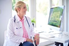 Female doctor portrait at the medical room. Beautiful smiling female doctor sitting in front of her computer at the doctor`s office and working royalty free stock photo