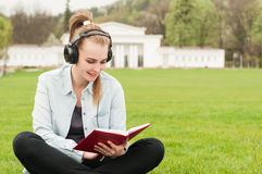 Beautiful smiling female enjoying music and reading in the park Stock Photo