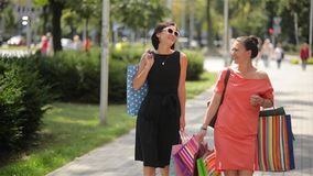 Beautiful smiling female friends with shopping bags in hands walking by street. Good mood stock footage